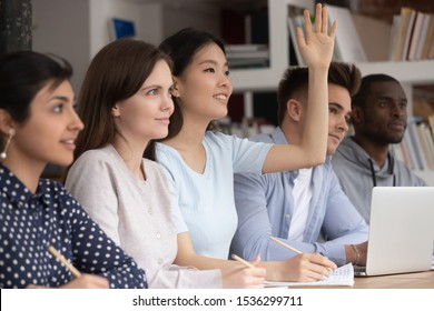 At lesson gathered multiracial students focus at asian schoolgirl sit together with schoolmates at desk raise hand want to answer or ask question, study process, gain knowledge and education concept