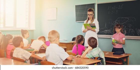 Lesson. Little schoolchildren are listening their teacher in class.