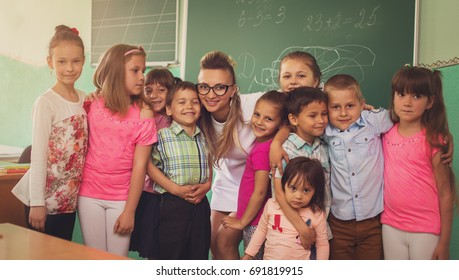 Lesson. Little schoolchildren are listening their teacher in class