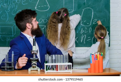 At the lesson. Male teacher giving private lesson to little children. Small schoolgirls reciting a lesson at chalkboard. Having school lesson in science classroom.