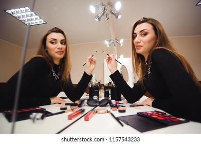 At the lesson in the school of visagistes, the girl does make-up herself