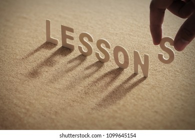 LESSONS wood word on compressed or corkboard with human's finger at S letter.