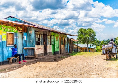 Lessos, Nandi Hills, Kenya, Oct 21, 2018: Roadside shopping area almost deserted on Sunday morning. Buildings are built from local timber and abandoned materials. Young man is watching milk vendor.