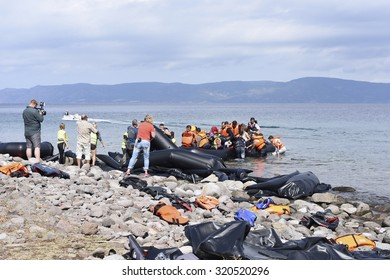 LESVOS, GREECE   SEPTEMBER 24, 2015: Refugees arriving in Greece by boat from Turkey. These Syrian refugees being filmed by reporters and journalists as their boat lands near Molyvos, Lesvos.