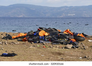 LESVOS, GREECE SEPTEMBER 24, 2015: Lifejackets discarded on a beach near Molyvos & rubber rings in the sea. Lesvos has been a hot spot for migrants & refugees arriving in boats, Turkey in background.