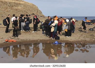 LESVOS, GREECE SEPTEMBER 24, 2015: A beach on Lesvos, Greece where many boats of refugees have arrived. Arriving refugees phone to family to let them know they are safe.