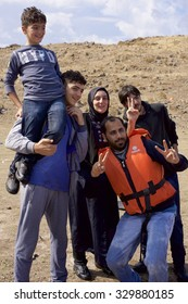 LESVOS, GREECE SEPTEMBER 24, 2015: A Syrian family celebrate and pose for photos having arrived safely after crossing from Turkey to a Greece. Lesvos has become a hot spot for arriving migrants.