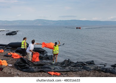 LESVOS, GREECE SEPTEMBER 24, 2015: Volunteers guide a refugee boat to shore as it arrives at the Greek island of Lesbos. This raft comes to shore near Molyvos, Lesvos (Mytilene) Greece.