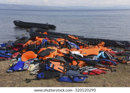 LESVOS, GREECE SEPTEMBER 24, 2015: Life Jackets discarded on a beach near Molyvos and rafts in the sea. Lesvos has been a hot spot for migrants and refugees arriving in inflatable boats from Turkey.