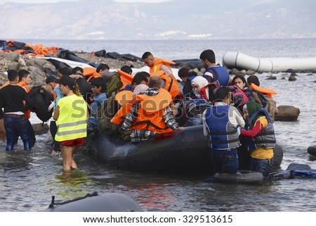 LESVOS, GREECE SEPTEMBER 24, 2015: Refugees arriving in Greece by boat from Turkey. These Syrian refugees are helped, by Norwegian volunteers, to land their boat near Molyvos, Lesvos (Mytilene).