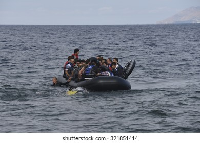 LESVOS, GREECE - SEPTEMBER 29, 2015: Refugees arriving in Greece by boat from Turkey. Volunteer lifeguards swam out to assist and guide the boat in when the motor failed.