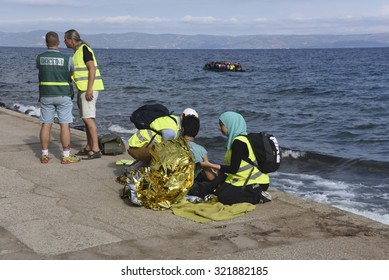 LESVOS, GREECE - SEPTEMBER 29, 2015: Refugee given help after being brought ashore by a volunteer lifeguard.  A refugee boat and Turkey seen in the background.