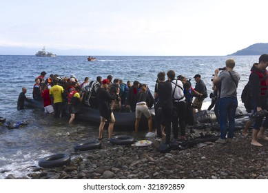 LESVOS, GREECE - SEPTEMBER 29, 2015: A refugee boat arriving on Lesvos is surrounded by volunteers and reporters. Lesvos has been a hotspot for, mainly Syrian, refugees arriving in Europe from Turkey