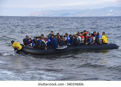 LESVOS, GREECE - SEPTEMBER 29, 2015: Refugees, escaping war and IS (ISIL), arriving in Greece by boat from Turkey. Volunteer lifeguards swam out to assist and guide the boat in when the motor failed.