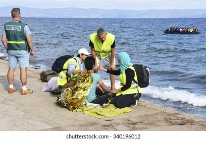 LESVOS, GREECE - SEPTEMBER 29, 2015: Refugee given help after being brought ashore by a volunteer lifeguard. A refugee boat and Turkey seen in the background. These Syrians are escaping from war & IS.