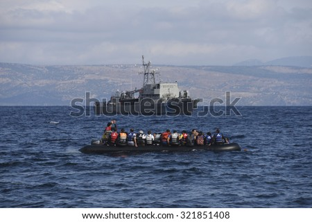 LESVOS, GREECE - SEPTEMBER 29, 2015: Syrian refugees arriving in Greece by boat from Turkey.  The Greek Coastguard is alerted when the motor fails. Turkey is seen in the background.