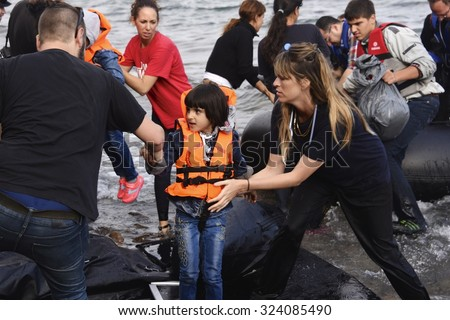 LESVOS, GREECE - SEPTEMBER 29, 2015: Syrian refugee child given help ashore, from volunteers, after crossing to Lesbos, Greece in an inflatable raft from Turkey.