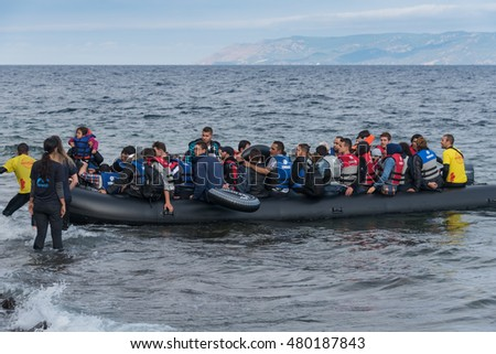 LESVOS, GREECE - SEPTEMBER 29, 2015: Refugees, escaping war and Islamic State, arriving in Greece by boat from Turkey. Volunteer lifeguards assist and guide the boat to shore when the motor failed.