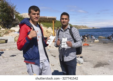 LESVOS, GREECE - SEPTEMBER 30, 2015: Refugee migrants from Afghanistan proudly show their tickets for the ferry from Mytilene, Lesvos to Athens continuing their journey through Europe.