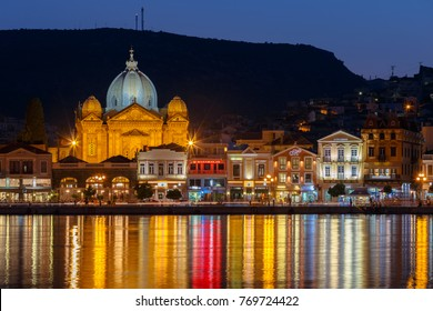 LESVOS ISLAND, GREECE - AUGUST 2017: Mytilene seafront with St Therapontas cathedral temple in the evening against a clear sky with the street lights and reflections at sea