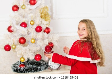 Let kid decorate christmas tree. Favorite part decorating. Getting child involved decorating. Girl long hair hold balls ornaments white interior background. How to decorate christmas tree with kid.