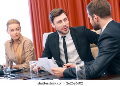 Let me explain. Young attractive business partners in formalwear discuss data sitting by the table at the meeting