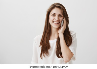 Let me finish this call. Studio shot of charming friendly girl with brown hair talking on smartphone and smiling broadly, gazing at camera, having conversation with best friend over gray background