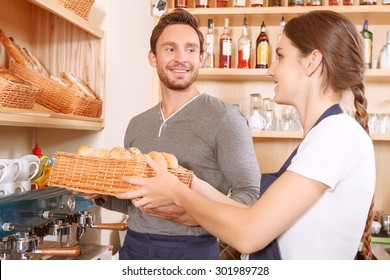 Let me help. Young handsome cafe worker is helping his female colleague to set out goods on stalls