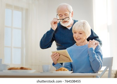 Let me look. Attentive senior man wrinkling forehead while looking downwards and standing behind his wife