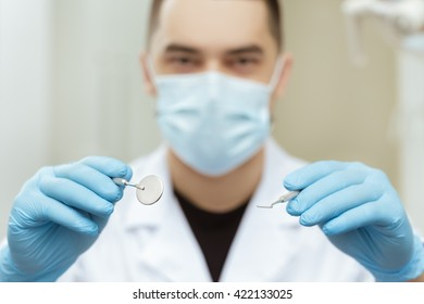 Let me see. Male dentist wearing surgical mask holding out dental tools to the camera selective focus