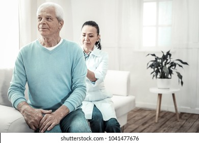 Let me see. Old serious grey haired man sitting in the bright room on the sofa showing his back to doctor and holding his hands on his knees.