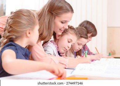 Let me see. Young attractive female teacher leaning to pupils and checking their work