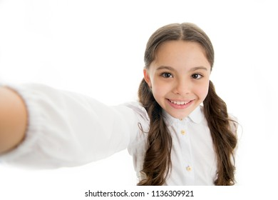 Let me take a selfie. Child girl school uniform clothes holds smartphone takes photo. Child school uniform kid happy face. Girl cute long curly hair holds smartphone taking selfie white background.