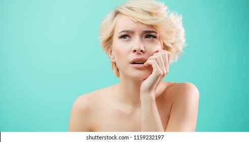 Let me think. close up portrait of doubtful, thoughtful beautiful woman looking aside and biting her lips.isolated blue background. awesome female trying to solve the problem.
