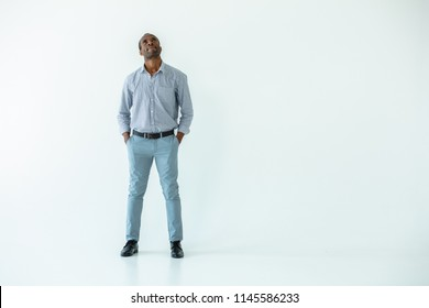 Let me think. Handsome adult afro american man being involved in toughts while standing isolated on white background