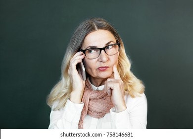 Let me think. Studio shot of thoughtful beautiful middle aged lady in stylish clothes and accessories holding finger on her cheek while talking on cell phone, having pensive facial expression