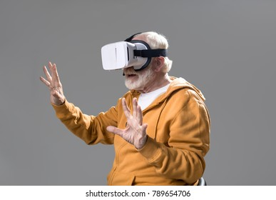Let me touch it. Waist up of playful senior entertaining himself while playing video games using virtual glasses. Isolated on grey background