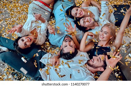 Let the party begin! Group of young people having fun together. Lying on the floor with confetti falling. Celebrating holiday in big company of close friends.