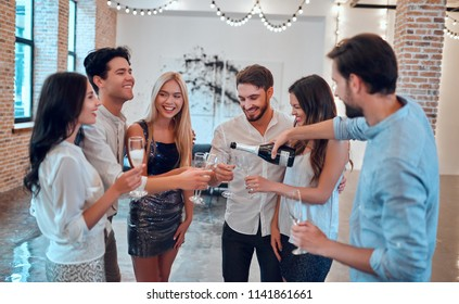 Let the party begin! Group of young people having fun together. Dancing in big light room with champagne. Celebrating holiday in big company of close friends.
