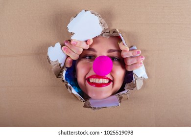Let `s play. A laughing young girl in a clown suit looks out of a torn cardboard box. 1 April Fools' Day concept.