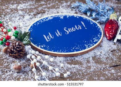 Let It Snow Written In Chalk On Blue Chalkboard Holiday Sign Background With Snow And Decorations.