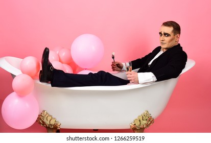 Let the tensions just drain off. Mime man has celebration party with food and drink. Mime actor enjoy bathing in bath tub. Comedian actor celebrate holidays. Bubble bath day. Bathing and relaxing.