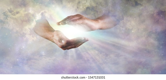 Let there Be Light Divine Concept -  God's hands emerging from beautiful clouds, cupped, with rainbow colored bright white star burst of light between and copy space