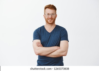 Let us get to business. Portrait of good-looking confident redhead mature guy with bristle in round glasses, holding hands on chest and smiling broadly, looking after employees in office