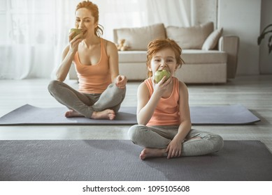 Let us take a bite. Full length portrait of woman and child sitting on carrymats and eating juicy fruits. They are having rest after home fitness looking exited and joyful
