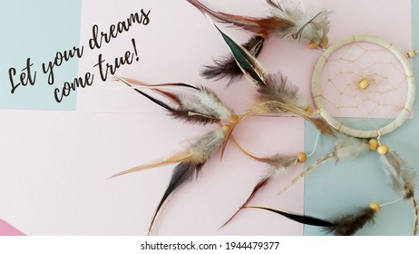 Let your dreams come true,beautiful dreamcatcher with brown bird feathers,threads and beads of rope hanging, dreamcatcher handmade lies on light pink and blue table next to an  inspiring text.