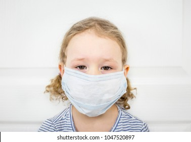 Lethargic young girl with blurry eyes has flu and is very sick, has medical face mask on. Fear of being contagious concept.