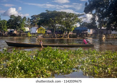 """Leticia - region Amazonas - Colombia, June 11, 2018: Small wooden canoes with an explosion engine called """"peque peque"""" are the public transport that travel along the Amazon River in Leticia, Colombia."""
