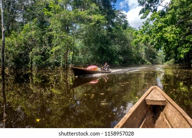 "Leticia - region Amazonas - Colombia, June 11, 2018: Small wooden canoes with an explosion engine called ""peque peque"" are the public transport that travel along the Amazon River in Leticia, Colombia."