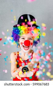 Let's celebrate! Funny kid clown playing at home. Child shooting party popper confetti. 1 April Fool's day concept